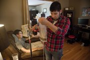 Hospice aide Anthony Alaniz Jr., 21, pours some Coke into a bag so Hiram Salvini can enjoy a cool beverage. Because of his ALS, Salvini has to eat through a feeding tube.