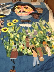 "A detail of African-Americans working in cornfields from Marla Jackson&squot;s quilt, ""Still We Rise,"" as Jackson worked to finish the project the week before the 150th anniversary of Quantrill&squot;s raid. Above are the faces of Quantrill, Bloody Bill Anderson and a free black man who rode with Quantrill, John Nolan."