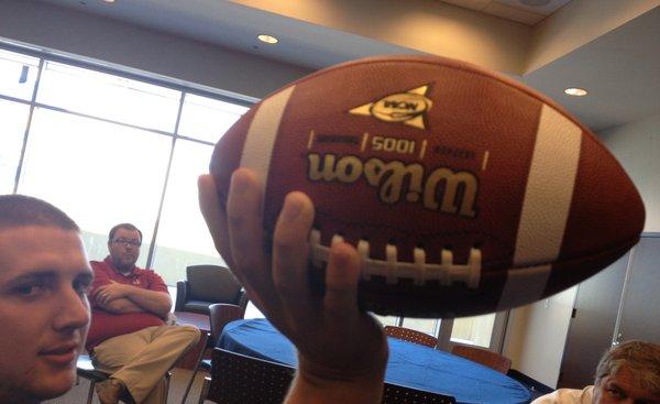 Underneath the ball.
