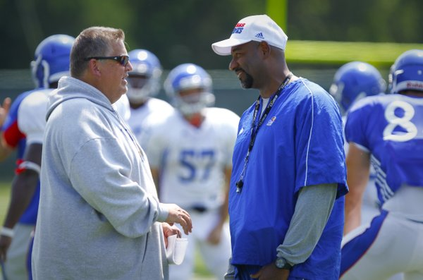 Kansas head coach Charlie Weis and defensive line coach Buddy Wyatt confer during practice on Tuesday, Aug. 20, 2013.