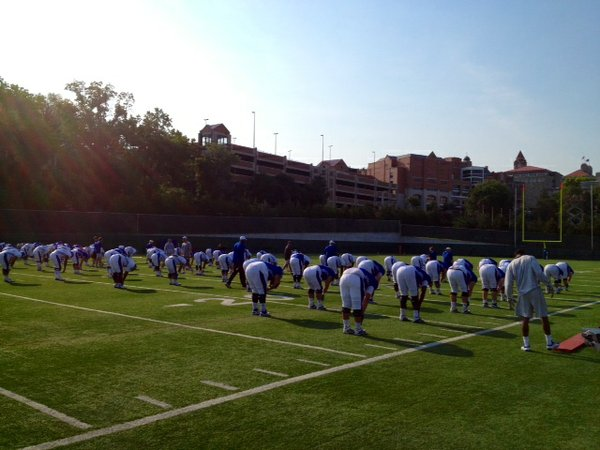 Signs of the early morning sun creep across the KU practice fields as the Jayhawks go through stretching Wednesday morning.
