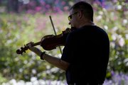 John Shaw, Lincoln, NB., practices near the flower bed in South Park before competing in the Open Fiddle competition at the 33rd Kansas State Fiddling and Picking Championships in South Park Sunday, August 25, 2013.