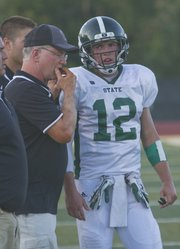 Free State football coach Bob Lisher talks with senior quarterback Joe Dineen (12) during the the Firebirds' fall sports jamboree, Thursday, Aug. 29, 2013, at FSHS.