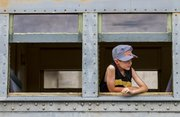 "Wearing a ""future engineer"" cap, seven-year-old Jack Barker, of Lee&squot;s Summit, Mo., looks out from a passenger car window while waiting to depart from the Midland Railway Depot in Baldwin City during the annual Railfest event Saturday."