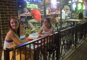 "KU seniors from Topeka, Kelly Wayner, left, and Bethany Hughes, eat on the patio outside Fuzzy&squot;s Taco Shop, 1115 Massachusetts St., after midnight Friday, August 30, 2013. ""It&squot;s sort of my go-to spot,"" said Hughes of the late-night food stop."