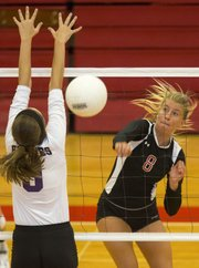 Lawrence High's Cienna Sorell (8) fires a shot past Blue Valley Northwest's Madison Rohr during their volleyball match Tuesday, Sept. 3, 2013, at LHS. The Lions lost, 3-0, in straight sets.
