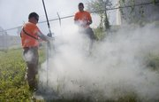 Kyle Forsythe, left, and Robby Hartpence, both field technicians for TREKK Design Group LLC, Kansas City, Mo., participate in a city sewer system test demonstration using smoke on Sept. 3, 2013. The test involved filling the sewer system, which may cause smoke to come out of manhole covers or even the roof vents of peoples' homes. That may cause people to mistakenly think their house is on fire.