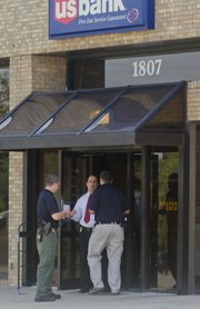 Lawrence police detectives respond to US Bank at 1807 W. 23rd St., Thursday afternoon, after a reported robbery.