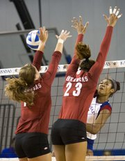 Kansas outside hitter Tiana Dockery slips a shot past Arkansas blockers Meredith Hays (11) and Summer Morgan (23) during their volleyball match Saturday at the Horejsi Center. The Razorbacks defeated the Jayhawks in five sets.