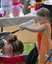 "Sophia Coons, 2, pours water on her mother Kala Coons&squot; head Sunday at the Fall Arts & Crafts Festival in South Park. The two were at Sophia&squot;s grandmother Betty Coons&squot; ""Babes & Beads"" booth."