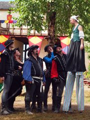 Claire Gurley chats with some of the other performers just after the opening cannon Sunday at the Kansas City Renaissance Festival. Claire will walk the festival grounds on her stilts a few times each weekend this season.