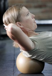 Becky Bridson, a Lawrence Yamuna practitioner, does some body-rolling exercises using balls of various sizes to slowing massage and stimulate her muscles.