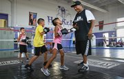 Volunteer boxing instructor Erik Riley jokes with eight-year-old Lucy Hardy as he teaches her how to throw a combination of jabs on Tuesday, Sept. 10, 2013 during a meeting of the Haskell Boxing Club. Also pictured are Sam Harjo, 10, and Cyrenity Hardy, 7.