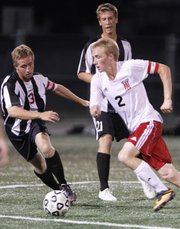 Lawrence High midfielder Connor Henrichs pushes the ball upfield against Blue Valley West midfielder Derek Bullis during the second half on Tuesday, Sept. 10, 2013 at Lawrence High School.