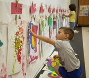 "Pre-school student Cole FitzGerald puts up his most recent work or art on the wall in his Lawrence Arts Center classroom Thursday, Sept. 12, 2013. The Arts Center&squot;s ""STEAM""-based curriculum overlaps areas of science, technology, engineering, arts and math for students."
