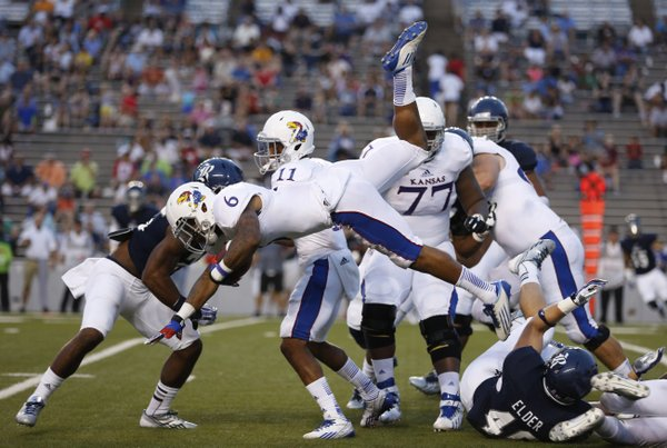 Kansas running back Darrian Miller is upended by Rice linebacker Nick Elder during the second quarter on Saturday, Sept. 14, 2013 at Rice Stadium in Houston, Texas.