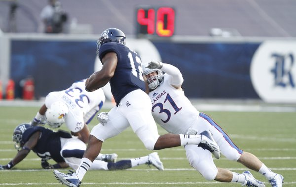 Kansas linebacker Ben Heeney reaches for Rice running back Charles Ross during the first quarter on Saturday, Sept. 14, 2013 at Rice Stadium in Houston, Texas.