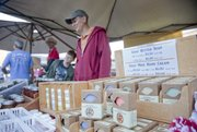Courtney Skeeba of Homestead Ranch in Lecompton and her son, Marek, sell their handcrafted goat butter soaps at the Lawrence Farmers Market.