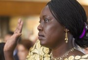 Originally from South Sudan, Ayak Mawin, of Olathe, takes the oath of citizenship during a naturalization ceremony Tuesday morning at the Dole Institute of Politics.