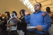 Originally from Colombia, Leonardo Polo, of Kansas City, takes the oath of citizenship during a naturalization ceremony Tuesday morning at the Dole Institute of Politics.