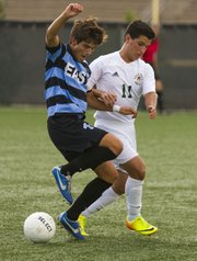 Free State sophomore forward Eduardo Carballido (11) and  Shawnee Mission East's Derrick McClanahan (1) get their arms locked up as they fight each other for control of the ball during their soccer match Thursday at FSHS.