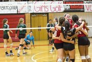Lawrence High players celebrate in the foreground following their volleyball victory over rival Free State Thursday at LHS.