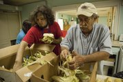 From left, Jim McDonald and Tyler Rice work their way through boxes of fresh corn. They were just two of the many volunteers preparing lunch at the L.I.N.K. kitchen on Thursday.