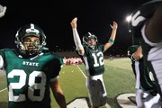 Free State's Paul Bittinger (28) and Joe Dineen (12) celebrate their 28-26 victory over Olathe East on Friday, Sept. 20, 2013, at FSHS.