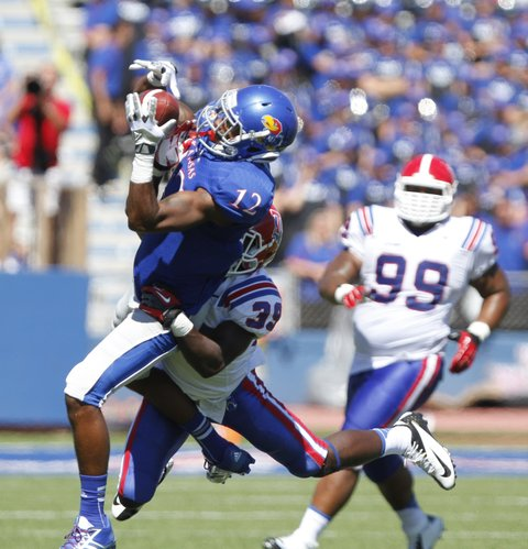 Kansas receiver Christian Matthews hauls in a pass with Louisiana Tech defensive back Xavier Woods on his back during the fourth quarter.