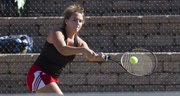 Lawrence High's Kendall Pritchard hits a backhand in her singles match on Monday, Sept. 23, 2013, at LHS.