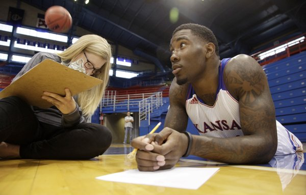 Alexandra Krzemien, video producer with Rock Chalk Video, ducks a loose basketball as she interviews sophomore forward Jamari Traylor during KU's men's basketball media day Wed. Sept. 25, 2013.