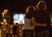 A couple stands in the middle of Massachusetts Street Thursday evening as they watch the 1980s movie, The Goonies, on a large, portable movie screen set up at 11th and Massachusetts Streets.