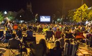 Hundreds of people flooded Massachusetts Street Thursday evening to watch the 1980s movie, The Goonies, on a large, portable movie screen set up at 11th and Massachusetts Streets.