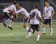 Lawrence High sophomore defender Piper Hubbell, left, celebrates his goal with teammate Jakob Burdett while Cale Bertrand (9) and Connor Henrichs (2) watch during their soccer match against Shawnee Mission West Thursday evening at LHS.