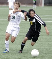 Free State sophomore Will Laufer (18) attempts to get past a Topeka High defender during a soccer game Saturday, Sept. 28, 2013 at Free State.