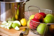 Roughly chop apples and put them in a large stock pot to make homemade applesauce.