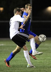 Lawrence High junior Jakob Burdett makes a play on Gardner Edgerton's Tim Mitchell (22) on Monday September 30, 2013.