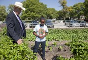 Richard Gwin/Journal World Photo.From  left, Dale Rodman Kansas Agriculture Secretary received a first hand look of West Junior HIgh's garden by West student Eyerusalem Zicker 14, as  State officials were in Lawrence on Tuesday October 1, 2013 as part of a Farm to School Celebration that focuses on eating healthy.