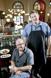 Chef/owner TK Peterson, standing, and owner Philip Wilson opened Merchants Pub & Plate, 746 Massachusetts St., in September.
