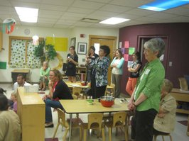 Visitors in Hilltop's preschool classroom listening to Mary Brownback read Pancake, Pancake by Eric Carle
