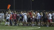 Lawrence High students storm the field following Lawrence High's victory over Free State Thursday at LHS. The Lions won, 2-0.