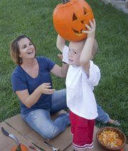 Kara Gourley and her son Chase, 4, play around with a pumpkin they just carved together outside their Lawrence home. Gourley, 37, a mother of three, had genetic testing and a double mastectomy done a few years ago because of a family history of cancer.