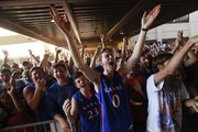 Kansas University junior Eli Birzer, Hutchinson, Kan., center, raises his arms in jubilation as Jayhawk newcomers Andrew Wiggins and Joel Embiid peek out of the fieldhouse to pump up the crowd before the doors opened for Late Night in the Phog, Friday, Oct. 4, 2013.