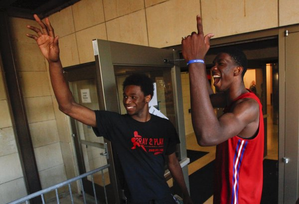Kansas newcomers Andrew Wiggins, left, and Joel Embiid peek outside to pump up the crowd before the fieldhouse doors opened for Late Night in the Phog, Friday, Oct. 4, 2013.