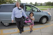 Howard Diacon, principal at Sunflower School, greets kindergartner Victoria Ma as she is dropped off at school Oct. 4. Diacon greets every student before school at the drop-off lane.