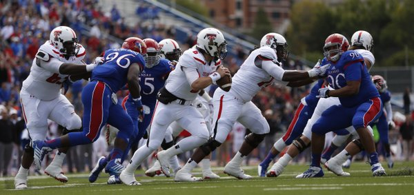 Kansas defenders chase after Texas Tech quarterback Baker Mayfield during the second quarter on Saturday, Oct. 5, 2013 at Memorial Stadium.