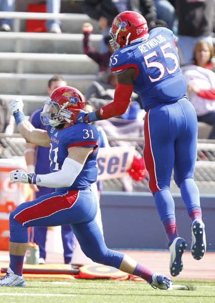 Kansas linebacker Ben Heeney celebrates a third-down stop against Texas Tech with buck Michael Reynolds during the second quarter on Saturday, Oct. 5, 2013 at Memorial Stadium. The stop for a loss forced a Tech field goal.