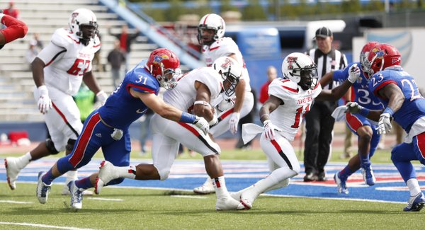 Kansas linebacker Ben Heeney (31) can't hang on to Texas Tech running back DeAndre Washington as he heads in for a touchdown during the third quarter on Saturday, Oct. 5, 2013 at Memorial Stadium.