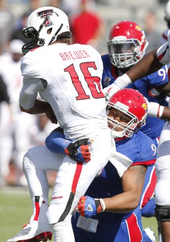 Kansas defensive lineman Tedarian Johnson brings down Texas Tech quarterback Michael Brewer during the fourth quarter on Saturday, Oct. 5, 2013 at Memorial Stadium.