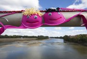 Volunteers spent part of Sunday afternoon hanging hundreds of bras across the east side of the Kansas River bridge as part of Bras Across the Kaw.